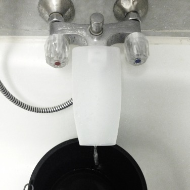 Tap / Faucet extension with a shampoo bottle