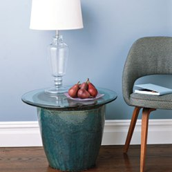 Supplement your assortment of occasional tables by bringing a tall planter indoors and topping it with a piece of glass.